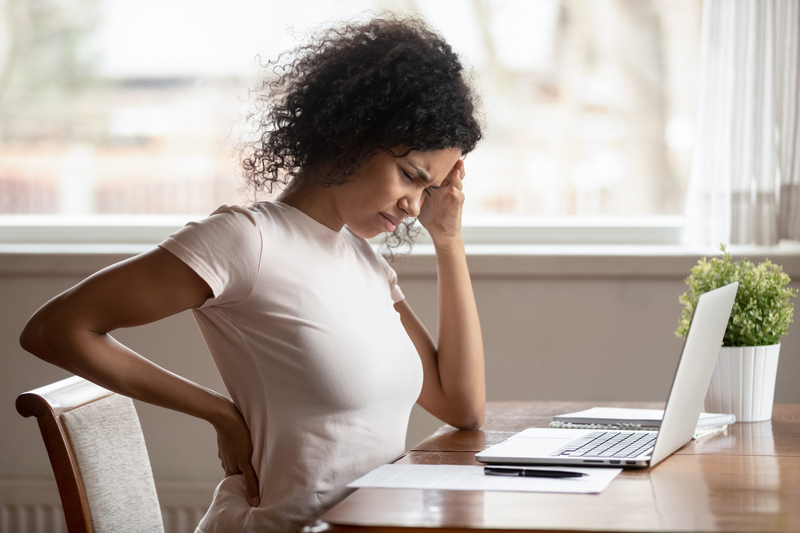 Unwell african American millennial woman sit at table work at laptop touch lower back suffer from incorrect posture, tired biracial female have painful feeling, struggle with backache or spine spasm